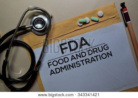Fda - Food And Drug Administration Text On Document Above Brown Envelope And Stethoscope. Healthcare