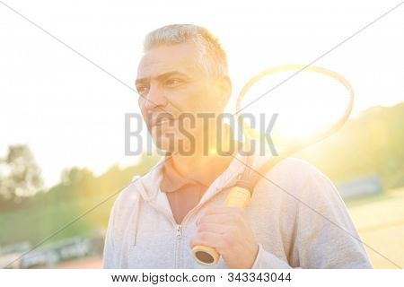 Mature athelete holding tennis racket while standing in court with yellow lens flare