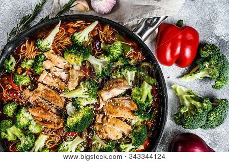 Asian Egg Noodles With Vegetables And Meat On Cooking Pan. Gray Background. Top View