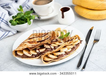 French Crepes With Chocolate Spread And Banana On White Plate. Sweet Food