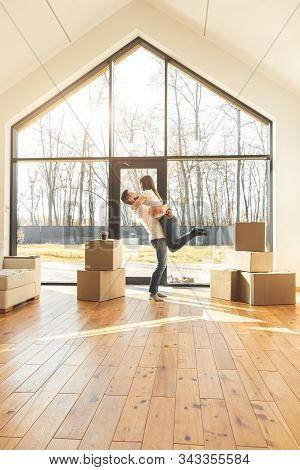 Young Couple Moves To A New Home. The Family Carries Boxes Of Things After Buying A Home.