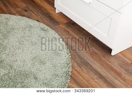 Detail Of Green Carpet On Wooden Floor In Living Room, Interior Decoration. White Closet