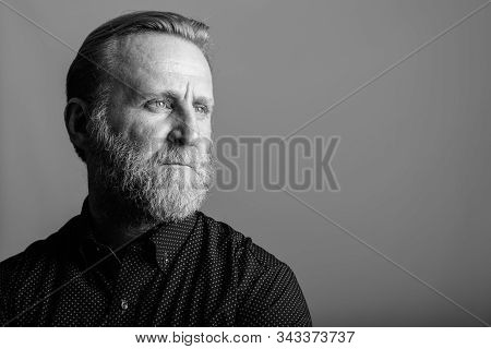 Studio Shot Of Mature Bearded Man Thinking While Looking Away In Gray Background