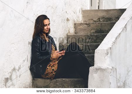 Woman Looking At Cell Phone. Woman Looking At Cell Phone While Sitting On Stairs. Woman Reading Mess