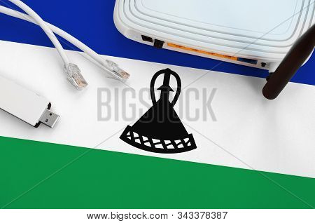 Lesotho Flag Depicted On Table With Internet Rj45 Cable, Wireless Usb Wifi Adapter And Router. Inter