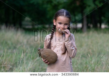Pretty little girl with beautiful dirty face sitting walking in summer forest and meadow holding a piece of stale bread and vintage flask. Orphan, child of war, poverty, hunger, famine, poor destitute