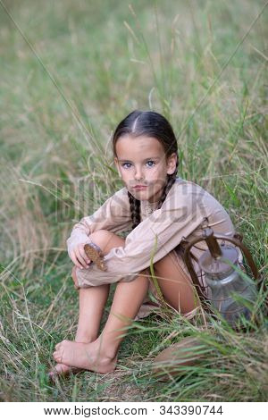 Pretty little girl with long pigtails and beautiful dirty face at summer meadow with vintage paraffin stove and eating stale bread. Orphan, child of war, poverty, hunger, famine, poor destitute kid.