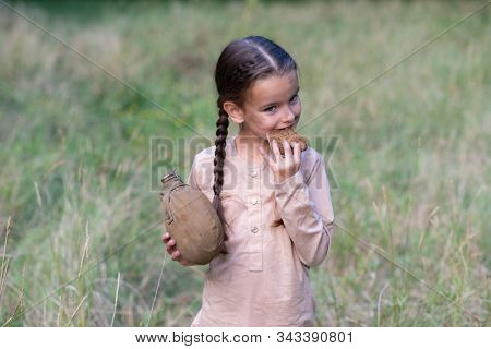 Pretty little girl with long pigtails and beautiful dirty face, holding a piece of stale bread and vintage flask. Orphan, child of war, poverty, hunger, famine, poor destitute kid.