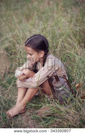 Pretty little girl with long pigtails and beautiful dirty face sitting at summer meadow with vintage paraffin stove. Orphan, child of war, poverty, hunger, famine, poor destitute kid.