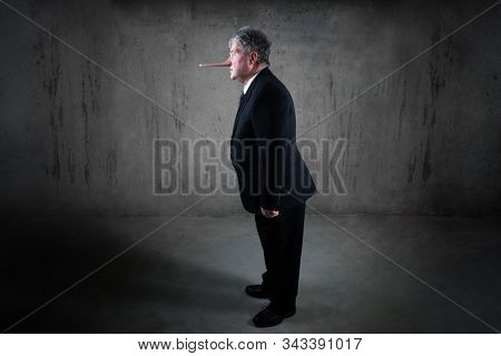 Lying businessman with a long nose standing in a suit, liar concept