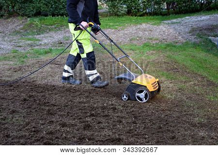 A Man Cuts Moss In The Garden With An Aerator. Concept: Lawn Aeration Before Planting Lawn Grass. Ga