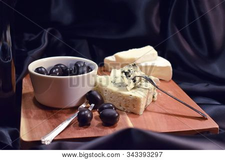 Olives And Two Kinds Of French Cheese On A Black Background. French Brie With White Mold, Cheese Wit