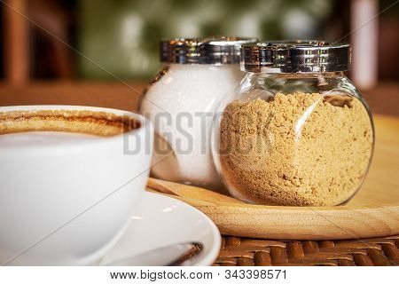 Sugar In Pot On Wood Plate Near Cup Of Coffee.