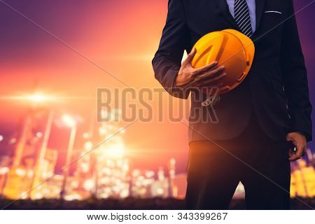 Construction Engineer In Business Suit  Holding Yellow Safety Hard Hat Security Equipment On Constru