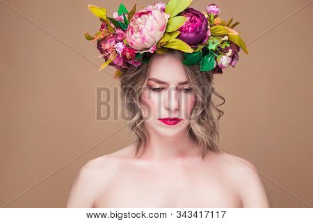 Beautiful Young Woman Model With Bright Flowers On Her Head On The Ocher Color Background