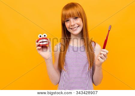 Beautiful Caucasian Woman With Red Hair Smiles And Recommend Brushes Teeth Isolated On Yellow Backgr