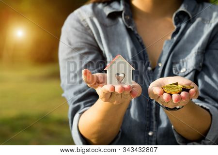 Money Cash And A Model Home In Woman Hand. Young Lady Hands Holding Little House Toy And Golden Coin