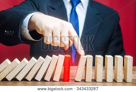 Businessman Restarts The Process Of Falling Dominoes. Start Work After Stopping. After The Weekend.