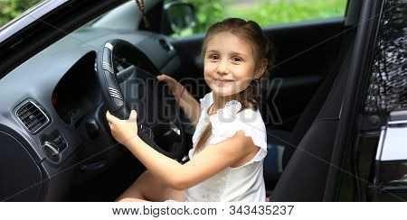 Happy Little Girl Sitting Behind The Wheel Of Dads Car