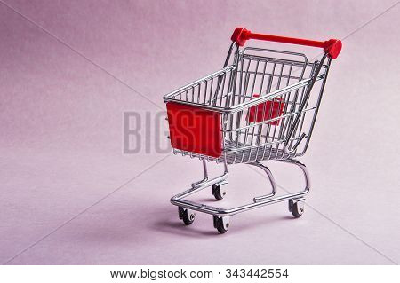 A Shopping Cart Or Trolly On Pink Background