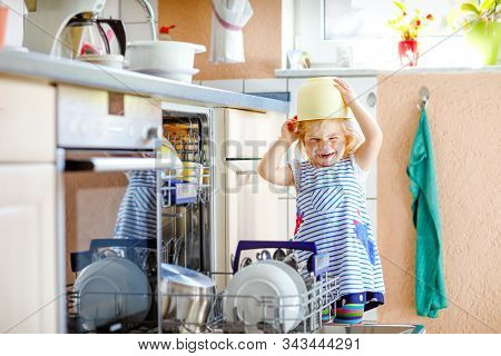 Little Adorable Cute Toddler Girl Helping To Unload Dishwasher. Funny Happy Child Standing In The Ki
