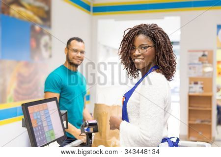 Smiling African American Cashier Standing At Checkout. Cheerful Young Woman With Dreadlocks At Workp