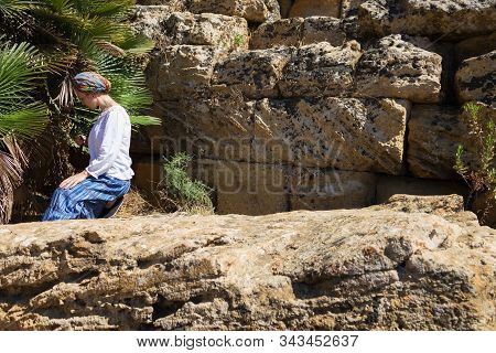 Woman In A White Blouse, A Long Skirt And A Turban. Woman Sits On Antique Ruins Near Palm Tree. The