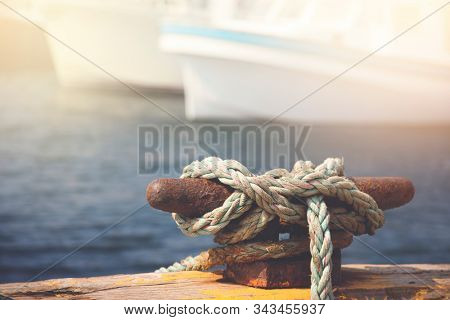 Quayside cleat and tied rope with boats moored in the background. Retro style matte processing.