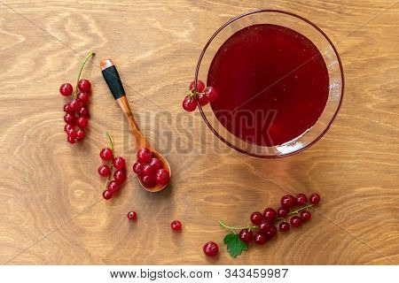 Glass Bowl Of Red Current Jam With Wooden Spoon Full Of Many Ripe Juicy Red Current Berries On Dark