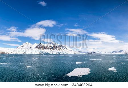 Panorama of the blue sky, blue glacier and snowy mountains and the ice floes and fjords of Svalbard, a Norwegian archipelago between mainland Norway and the North Pole