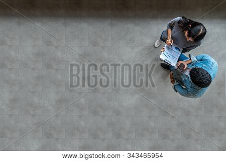 Top View Of Young Asian Business Team Standing, Talking And Reporting With Annual Report Document In