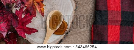 Maple syrup sweet ingredient for desssert recipes, liquid dripping from wooden spoon on wood log rustic sugar shack banner panoramic with buffalo plaid and red leaves.