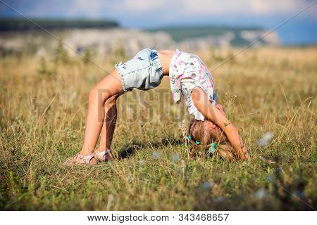 A Little Girl Makes A Bridge, Bending Her Back In Nature. A Flexible Child, Doing Gymnastics Exercis