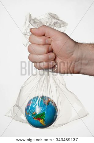 A Human Hand Holding The Earth In A Transparent Plastic Bag.
