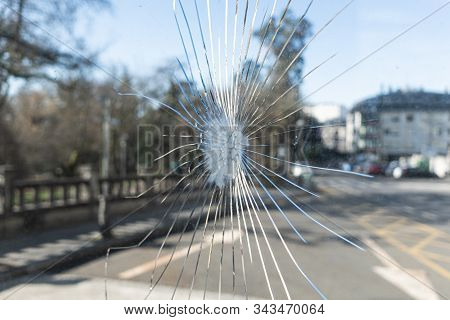 Broken Glass With Cracks And Blurred City Background. Vandalism Concept Or Social Problems