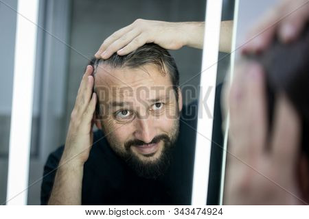 Man in front of mirror checking hair and skin
