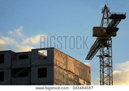 An Old Construction Crane And Unfinished Panel Multifamily House At The Frozen And Abandoned Constru