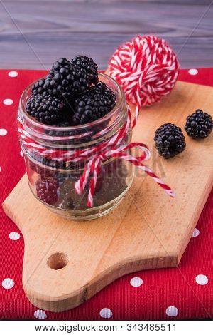 Transparent Jar Of Blackberries. Red And White Clew Thread With Knot.