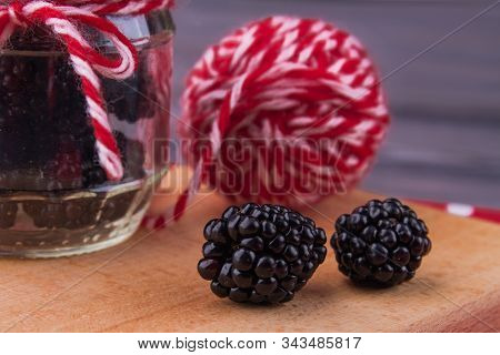 Two Fresh Ripe Blackberries Close-up. Clew And Jar Background.