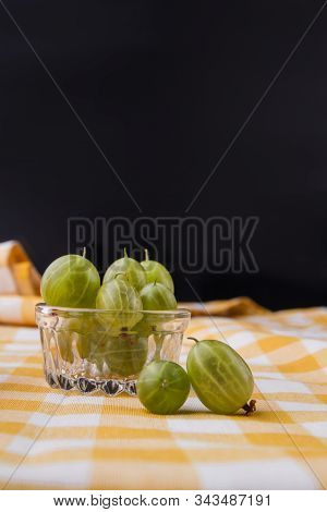 Small Glass Cup Overfilled Cherry-cherry-plums. Black Background.