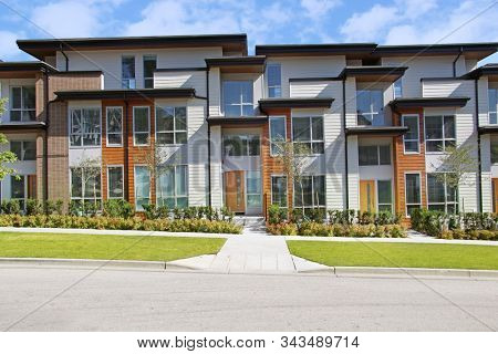 Brand new Contemporary townhomes in the suburbs of Surrey, B.C. Canada. Facade of attached homes with a sidewalk leading to small front yard.