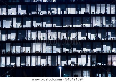 Office Building At Night. Late Night At Work. Glass Curtain Wall Office Building. Office Building Ex