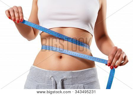 A Young Slender Woman Measures Her Waist With A Centimeter Tape. Isolated On White Background. The C