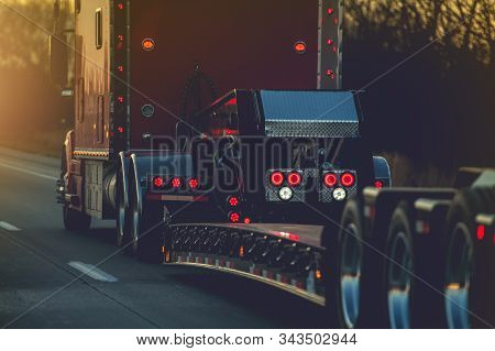 Semi Truck With Heavy Duty Platform Trailer On A Route. Transportation Industry.