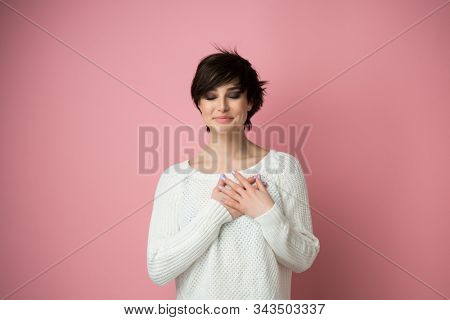 Young pretty woman smiling with hands on chest and grateful gesture on face. Happy woman feels grateful, hopes for successful plan realization, believes in success, wishes dream come true.