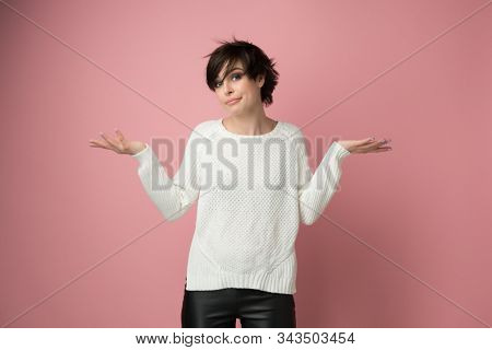 Beautiful young woman with nothing to do gesture, studio shot over pink. Pretty girl with expressive facial expressions using language of body to say apologies, regret, failure, fail, helplessness