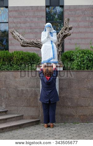 TIRANA, ALBANIA - MAY 03, 2019: A woman prays in front of the statue of St. Mother Teresa in front of St. Paul's Cathedral in Tirana, Albania