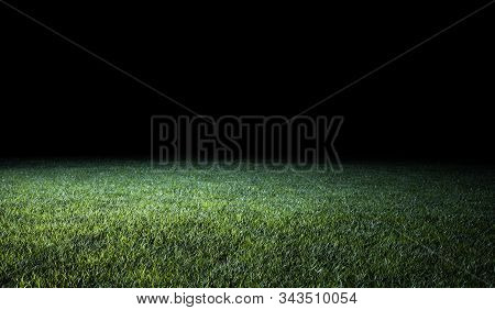 Low angle view across the neatly cut green grass of a lawn or sports field in shadowy evening light for use as a background image poster