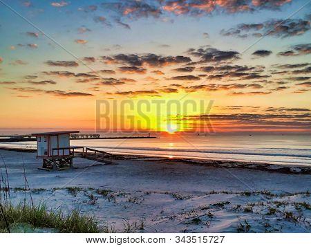 Peaceful Sunrise View Of A Lifeguard Shack Near The Ocean
