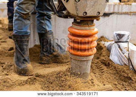 Closeup View Of A Person Operating A Vibratory Earth Rammer Compacting The Ground After Installation
